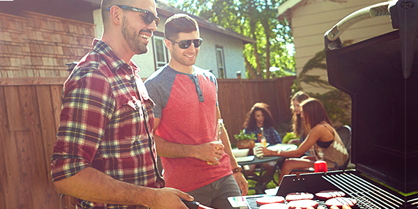 Men around a barbecue with women around a table